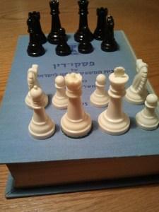 """תמונה של כלי שחמט מסודרים על כרך פד""""י של בית משפט עליון"""